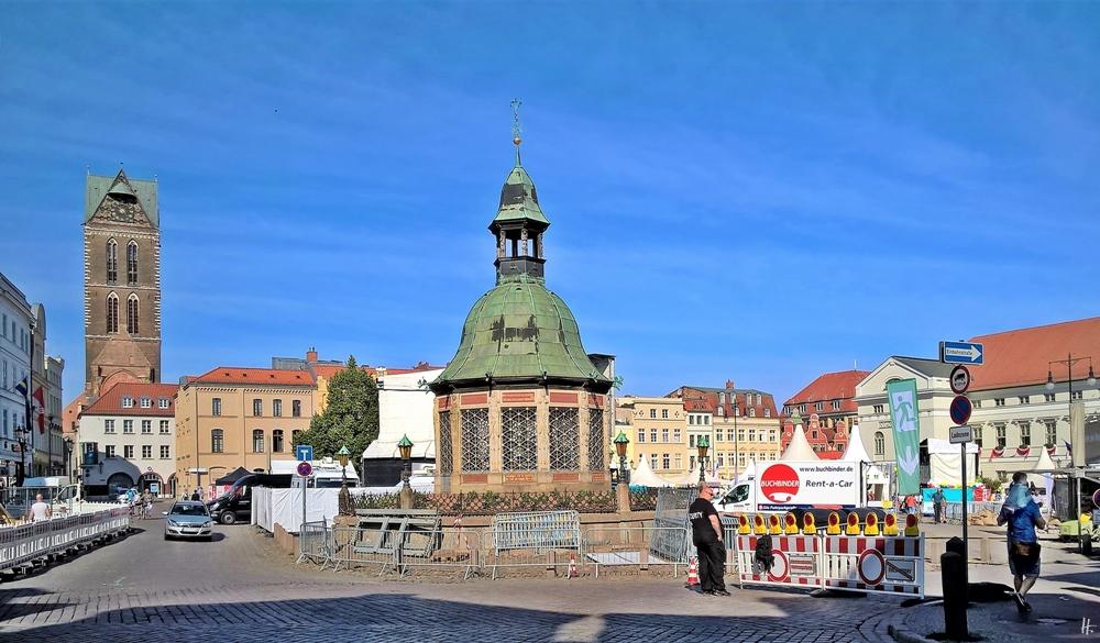 2018-08-18 hab elf in WISMAR, Am Markt - Wasserkunst, Marienkirchturm (links), Schwedenfest-Aufbauten und - Absperrungen, Rathaus (rechts)